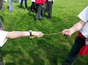 Playing tug of war with home-made bramble rope at Chipping Warden school